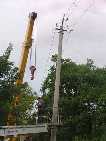 The electrician in cradle rises for repair of high-voltage column №607