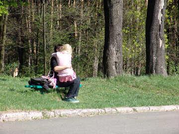 Liebespaar küssend auf einer Bank im Park im Frühjahr №550