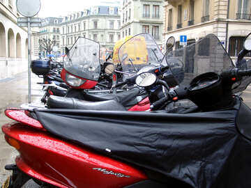 Motorcycles and mopeds are parked in the rain. №382