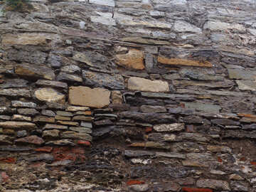 Ancient stone wall made of different materials with traces of frequent repair №358
