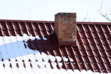 Brick chimney flue in the roof in winter metallocherepichnoy №497