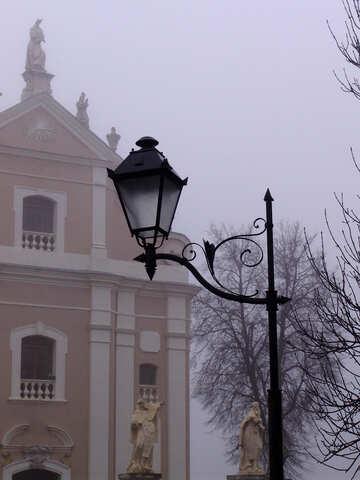 Старый уличный фонарь на фоне здания со скульптурами №343