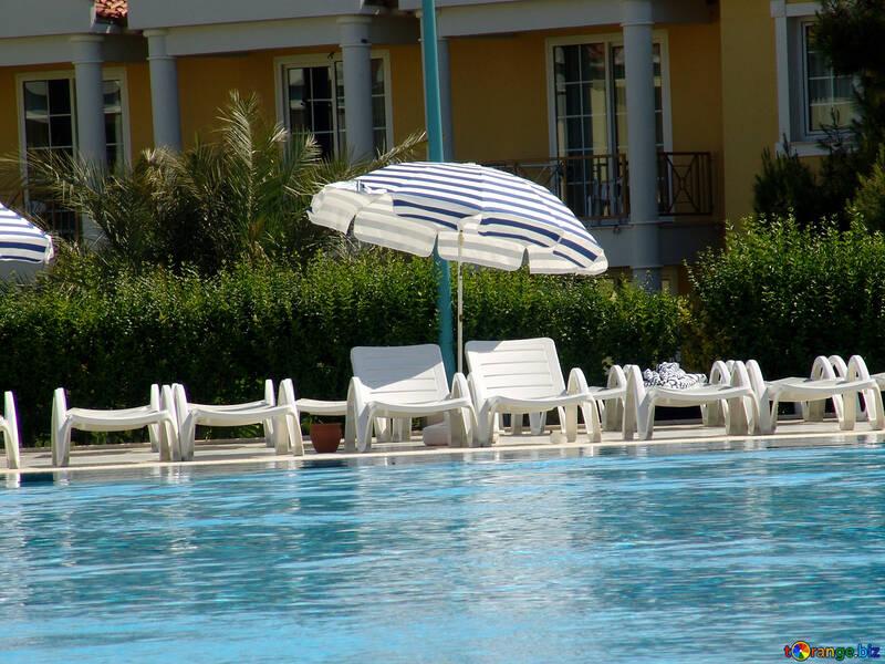 Zwei Liege unter einem Sonnenschirm am Pool №256