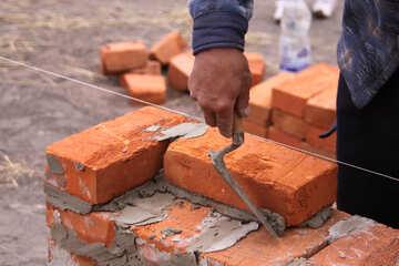 Mason in hardhat building brick №2934