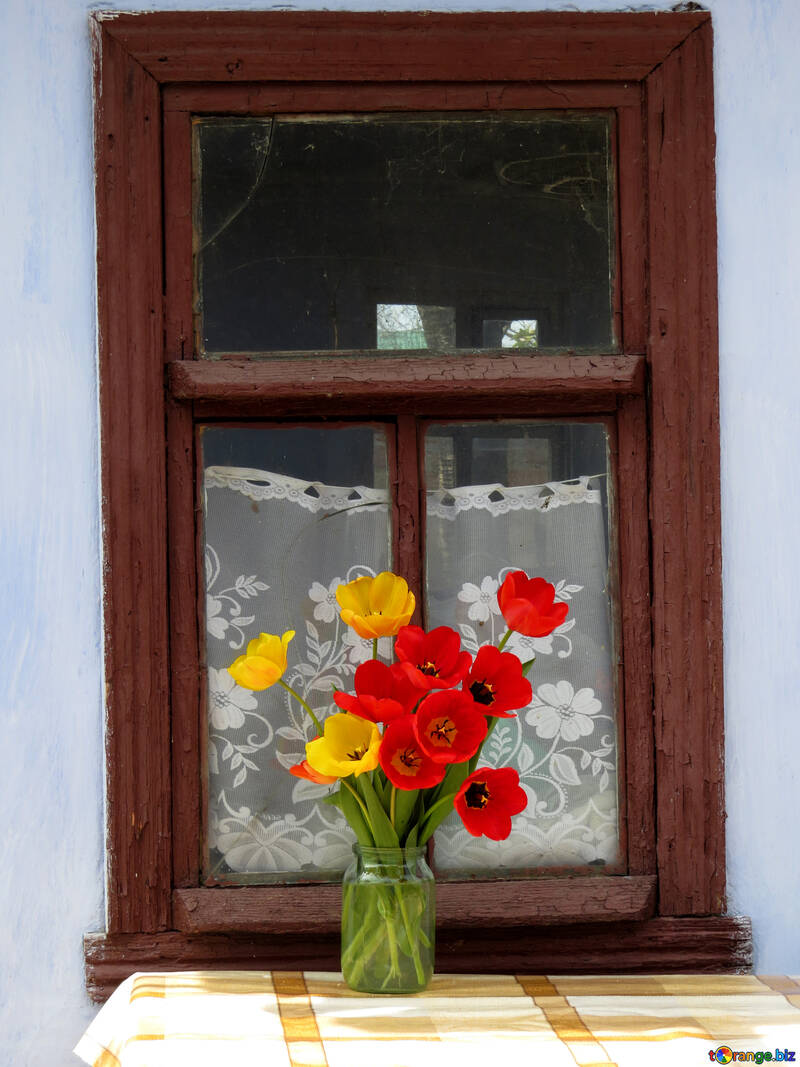 Bouquet of tulips on the table against the background of the rural old window №24138