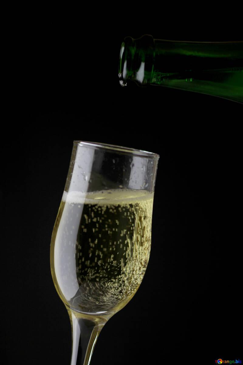 Champagne se vierte en un vaso burbujas de champán en el cristal ...