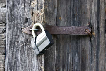 A modern padlock on an old wooden door  №3291