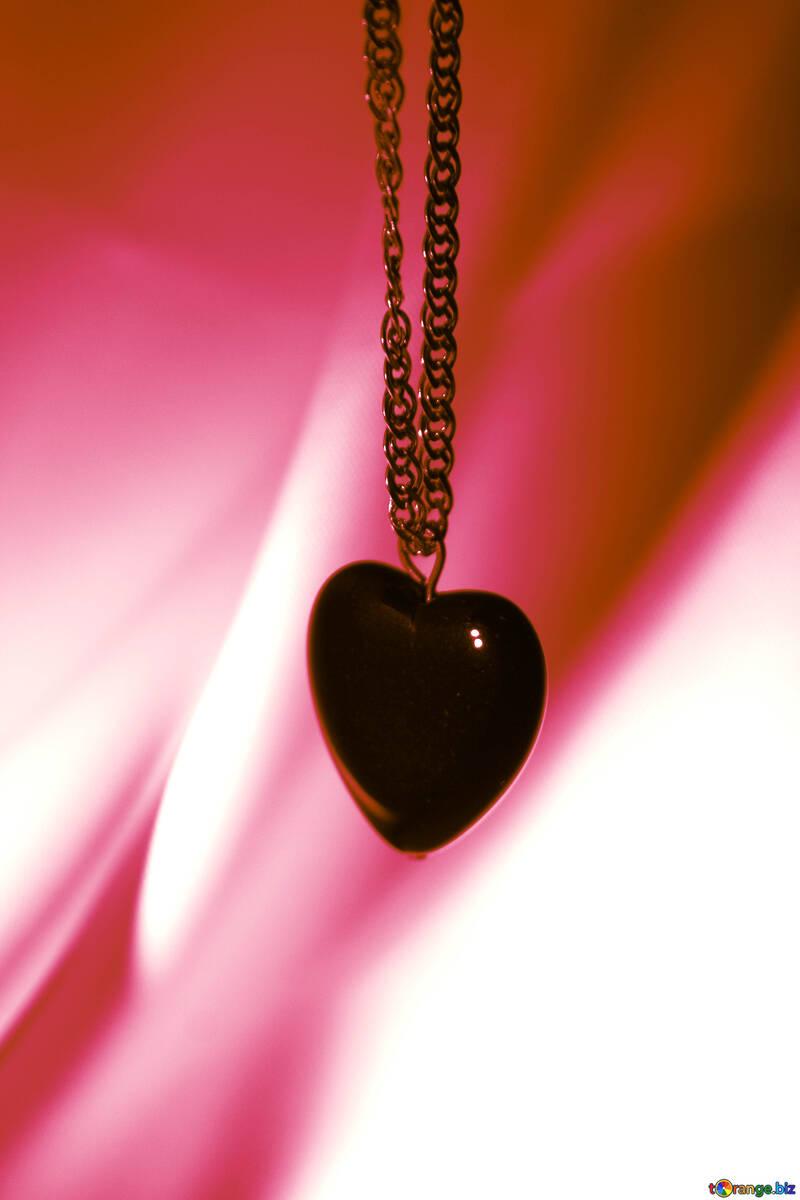 Herz schwarz an einer goldenen Kette auf rotem Grund №3576