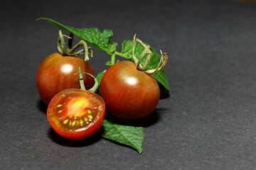 Tomatoes on dark background with leaves №32893