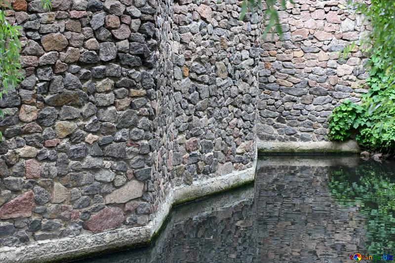 La pared de la fortaleza con un foso de agua №45979