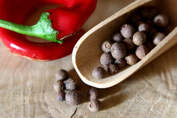 Black pepper and red pepper on a wooden table