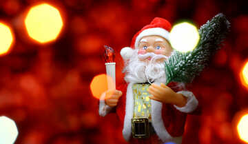 Santa Claus toy brings Christmas tree at glow red bokeh background and blurred lights foreground. Big Copyspace concept New Year`s market banner, poster.