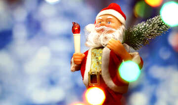 Santa Claus toy brings Christmas tree at blue snowy night bokeh background and blurred lights foreground. Red lantern torch to light the way. Big Copyspace concept New Year`s market banner, poster. №48161
