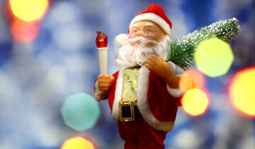 Santa Claus toy brings Christmas tree at blue snowy night bokeh background and blurred lights foreground. Red lantern torch to light the way. Big Copyspace concept New Year`s market banner, poster. №48163