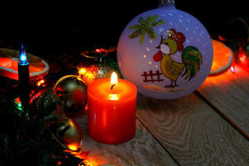 Christmas candle and ball cock with a symbol of the year on a wooden background №48189