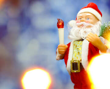 Santa Claus toy brings Christmas tree at blue snowy night bokeh background and blurred lights foreground.  №48159