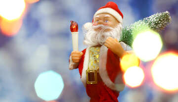 Santa Claus toy brings Christmas tree at blue snowy night bokeh background and blurred lights foreground. №48164