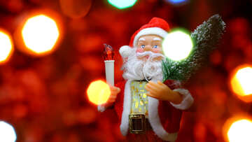 Santa Claus toy brings Christmas tree at glow red bokeh background and blurred lights foreground.  №48171