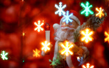 Santa Claus toy brings Christmas tree at glow red bokeh background and blurred lights snowflakes foreground.  №48174