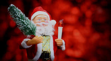 New Year`s card with Santa Claus toy brings Christmas tree at glow red bokeh background №48172