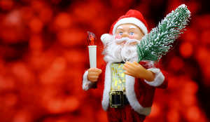 New Year`s card with Santa Claus toy brings Christmas tree at glow red bokeh background . Big Copyspace concept for New Year`s market banner, poster, congratulations. №48165
