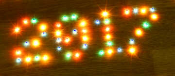 2017 new year on wooden desk table background. Number and frame border from colorful brights lights lamp bulb. №48147