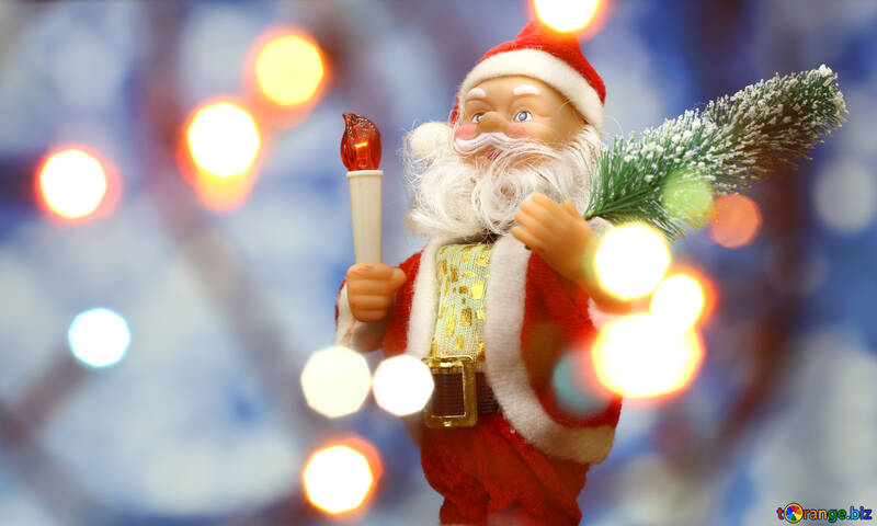 Santa Claus toy brings Christmas tree at blue snowy night bokeh background and blurred lights foreground. Red lantern torch to light the way. Big Copyspace concept New Year`s market banner, poster. №48162