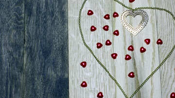 Red candy hearts surrounded by a green outline on a wooden background №49234