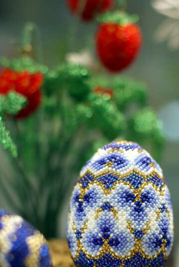 Easter egg decorated with beads on the background of flowers №49164
