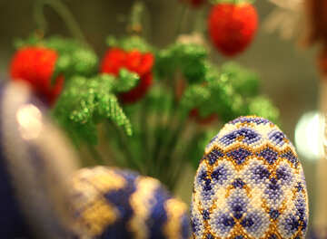 Easter egg decorated with beads on the background of flowers №49165