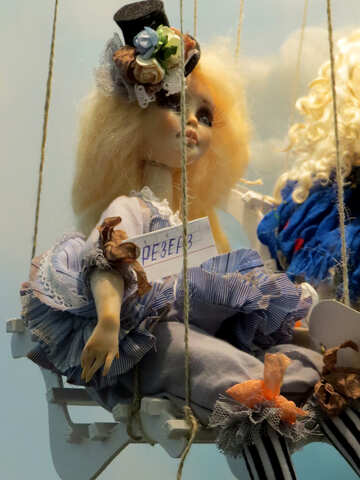 A fancy doll with puffy blond hair sitting on a swing №49067