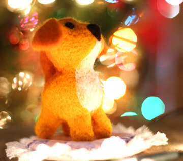 Symbol of new years 2018 yellow puppy mongrel dog. New years greetings background. Fancy handmade toy from wool on bokeh Christmas background. Place for insert logo or write text. Copyspace for congratulations. №49631