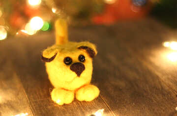 Symbol of new years 2018 yellow puppy dog. New years greetings background. Fancy handmade toy from wool on bokeh Christmas background. Place for insert logo or write text. Copyspace for congratulations. №49604