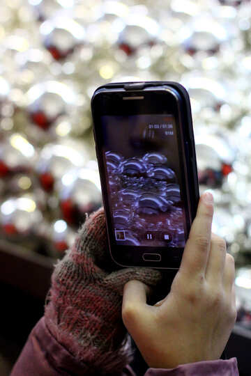 Hands holding the phone on the background of Christmas decorations №49479
