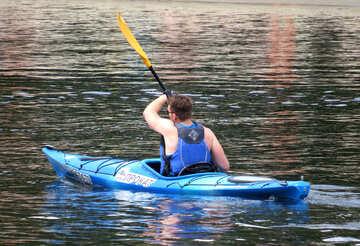 Ein Mann schwimmt entlang eines Flusses in einem Boot mit Rudern №49916