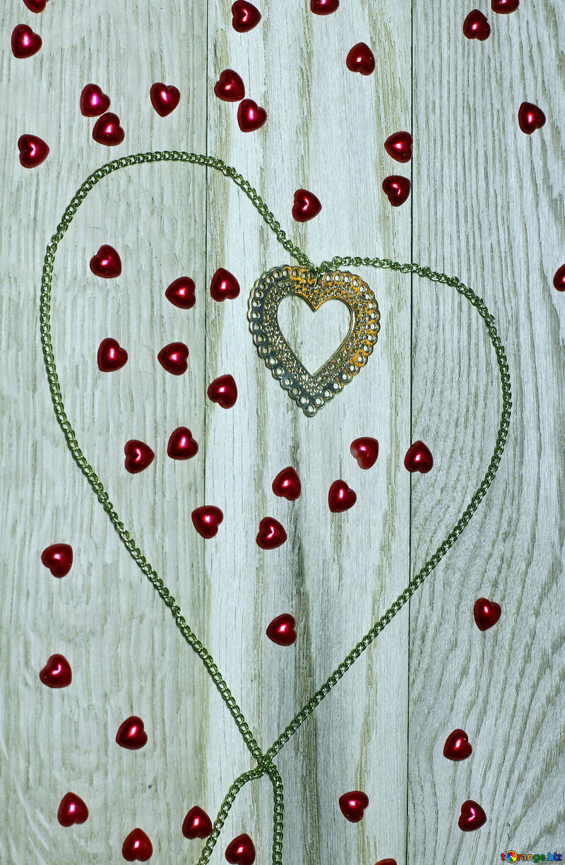 A necklace with a heart pendant on a wooden board with little red hearts all around №49235