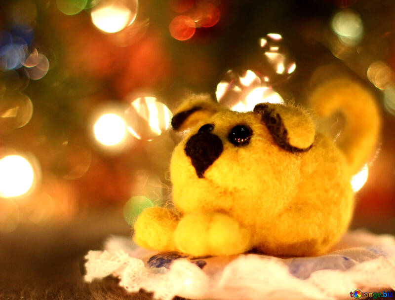 Symbol of new years 2018 yellow puppy. New years greetings background. Fancy handmade toy from wool on bokeh Christmas background. Place for insert logo or write text. Copyspace for congratulations. №49626