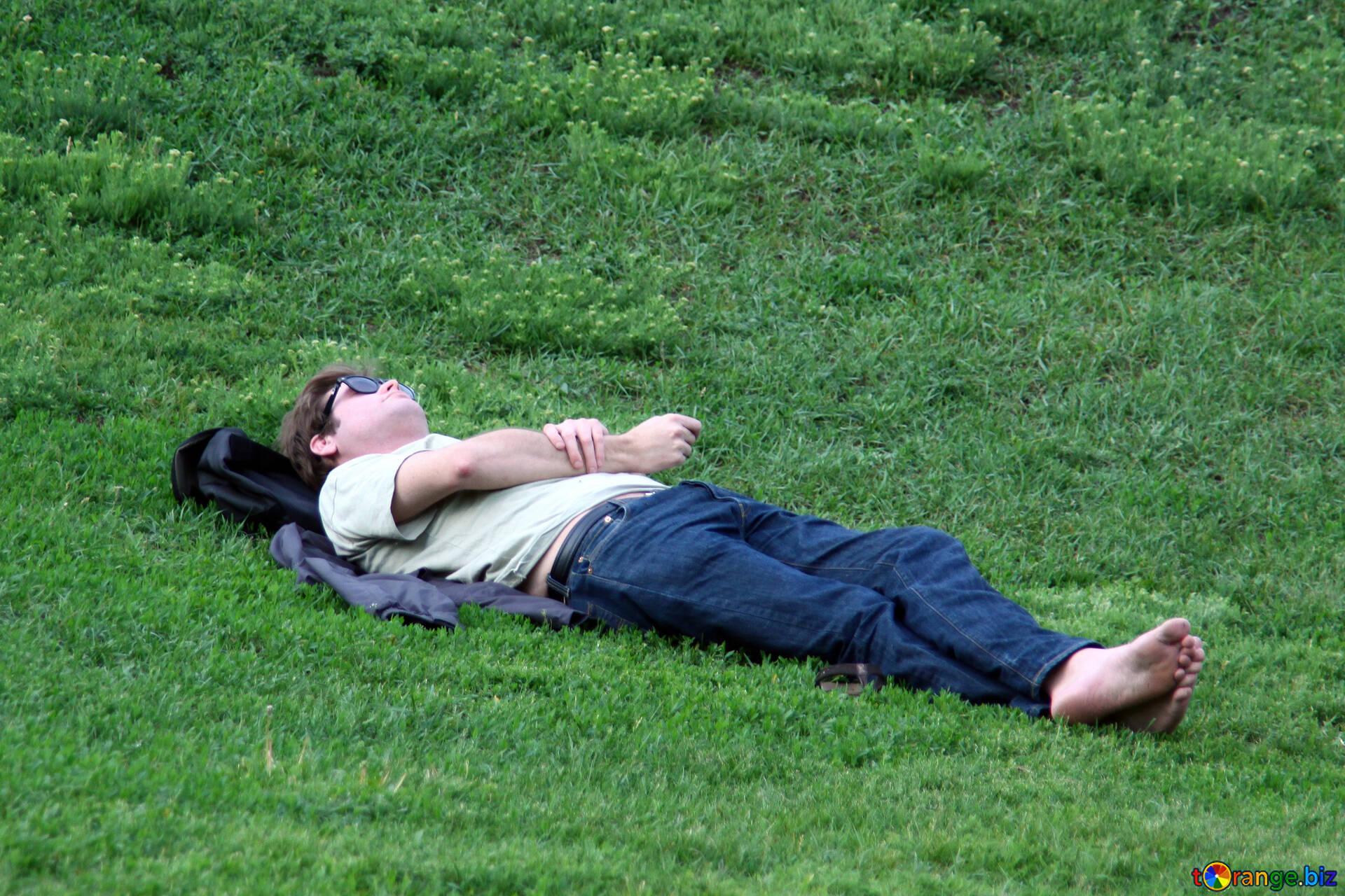 Люди отдыхают на природе мужчина лежит на траве босиком. отдых № 5091