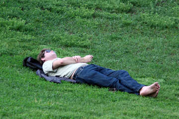 Man lying on the grass barefoot. №5091