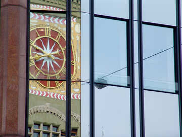 Reflection of ancient clock on the facade of a new building №50121