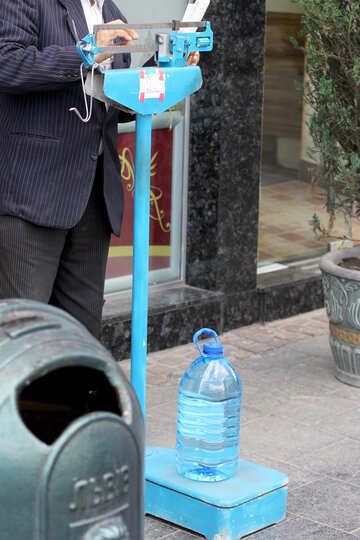 A gentleman who settles a blue balance where there is a bottle of water №51811