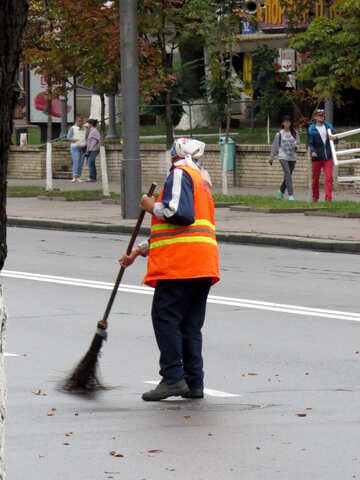A man sweeping the leaves off the road №51244