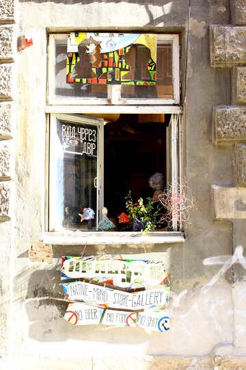 Ein offenes Fenster mit Blumen im Fensterbrett und ein Bild darüber №51675