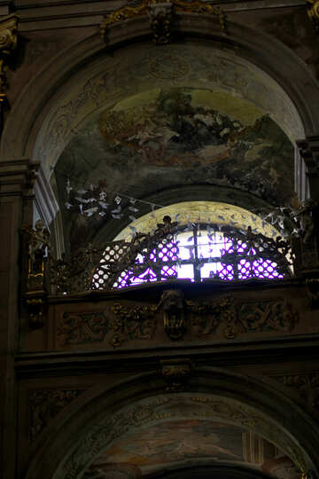 There is a bright light coming out of a stained glass window, this looks like a church. №51869
