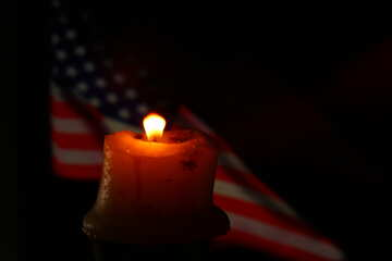 a candle lighted and an american flag in the background №52483