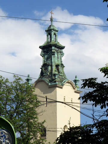 A green tower atop a butter colored building in front of a blue sky and white fluffy clouds church №52298