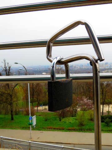 A lock on a window with the view of a city in the background padlock locker №52430