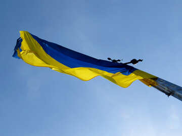 A bottom view of a blue and yellow flag with a blue sky in the background with very thin cloud №52081