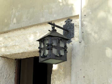 a lantern over a door on white wall torch №52313
