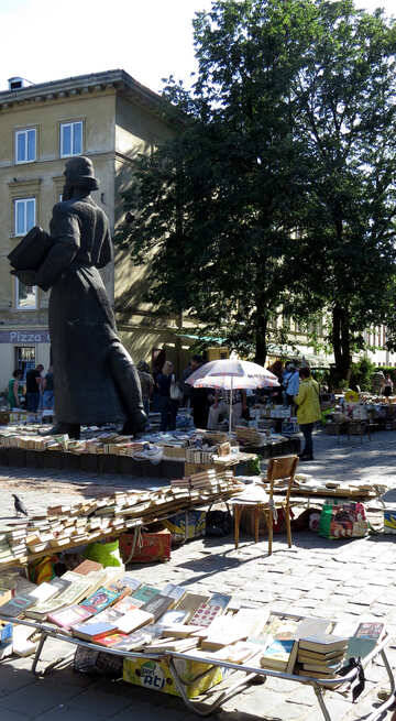 A park with a statue and tables statue with book tree and building №52154